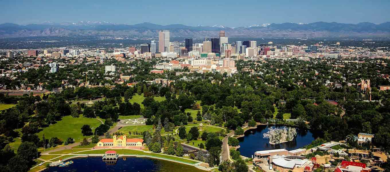 Denver Skyline panoramic facing Rocky Mountains under cloudy blue skies